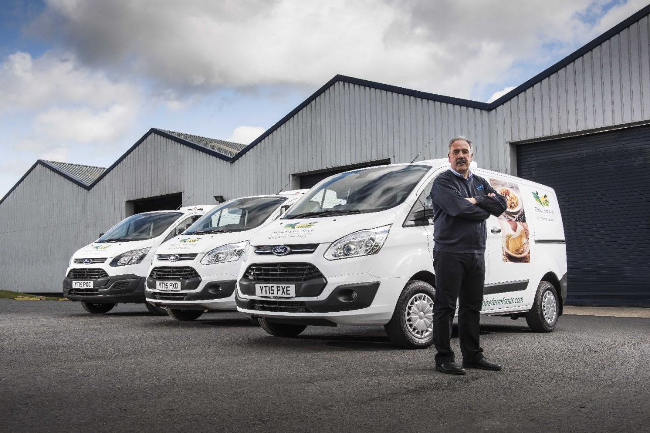 Mark Foster, managing director, Vanfridge Ltd, stands in front of three converted Transit Customs